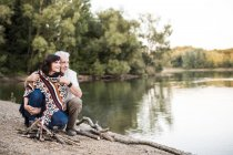Senior couple at campfire at a lake — Stock Photo