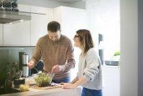 Pareja feliz preparando ensalada en la cocina juntos - foto de stock