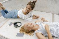 Две счастливые молодые женщины лежат на рампе в скейтпарке с маленькой гитарой, смартфонами и наушниками — стоковое фото