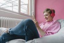 Улыбающаяся женщина сидит в мешке с сотовым телефоном и наушниками — стоковое фото