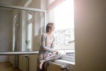 Mulher madura olhando pela janela — Fotografia de Stock
