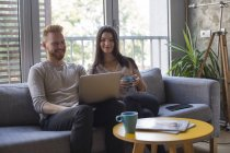 Couple sitting on couch looking at laptop — Stock Photo
