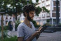 Uomo guardando tablet in città al crepuscolo — Foto stock