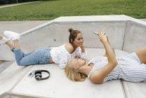 Два щасливих молодих жінок з мобільного телефону і навушники відпочив в скейтпарк — стокове фото