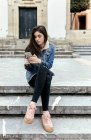 Young woman sitting on stairs in a town checking her smartphone — Stock Photo