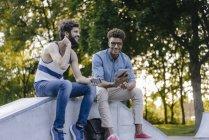 Два счастливых мультикультурных друга сидят в скейтпарке с мобильными устройствами — стоковое фото