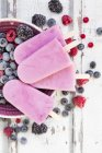 Homemade wild-berry ice lollies with raspberries, blueberries, red currants and blackberries in a bowl — Stock Photo
