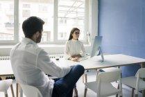 Homem que senta-se oposto à mulher e usando o computador no escritório — Fotografia de Stock