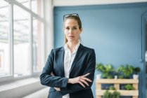 Businesswoman standing at home, with arms crossed — Stock Photo