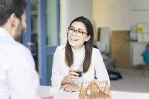 Женщина смеется над мужчиной с архитектурной моделью на столе — стоковое фото