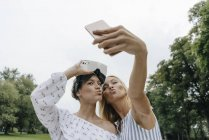Duas jovens mulheres com óculos VR tirando selfie em um parque — Fotografia de Stock