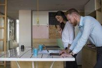 Lächeln Mann mit Frau mit Laptop auf dem Tisch zu Hause — Stockfoto