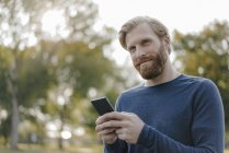 Ritratto di uomo caucasico che usa il cellulare in un parco — Foto stock