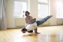 Femme mûre utilisant la tablette sur le dos de l'homme faisant handstand — Photo de stock