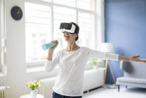 Vital woman at home cleaning and wearing VR glasses — Stock Photo