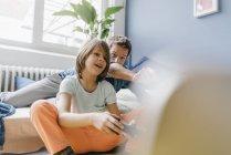 Padre e hijo jugando videojuegos juntos en casa - foto de stock
