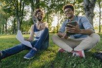 Два счастливых мультикультурных друга сидят в парке с мобильным устройством и бумагами — стоковое фото