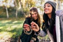 Due donne felici che tengono scintille in una foresta autunnale — Foto stock