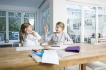 Dos chicas haciendo deberes en la mesa juntas chocando los cinco. - foto de stock