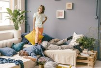 Son defeating father in pillow fight at home — Stock Photo