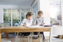 Дві дівчини роблять домашнє завдання на столі разом за допомогою планшета — стокове фото