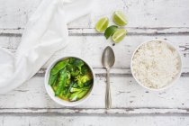 Green thai curry with broccoli, pak choi, snow peas, baby spinach, lime and rice — стоковое фото