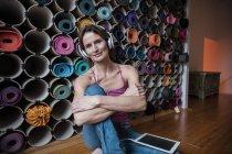 Портрет улыбающейся зрелой женщины, слушающей музыку перед ассортиментом ковриков для йоги — стоковое фото