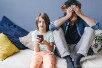 Padre che indossa la maschera scimmia seduto accanto al figlio usando lo smartphone a casa — Foto stock