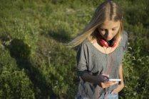 Giovane donna che utilizza il telefono cellulare sul prato — Foto stock
