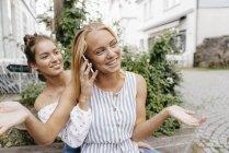 Две счастливые девушки с мобильным телефоном в городе — стоковое фото