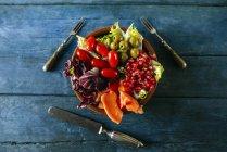Papaya salad, pomegranate, lettuce, tomato, olives and endive on blue wood — Stock Photo