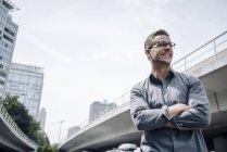 Portrait de jeune homme d'affaires riant les bras croisés à l'extérieur — Photo de stock