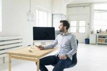 Uomo d'affari con cellulare seduto alla scrivania in ufficio — Foto stock