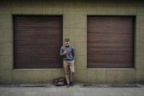 Молодий чоловік прихилився до будинку і користувався мобільним телефоном. — стокове фото