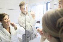 Immagine speculare di coppia lavarsi i denti in bagno a casa — Foto stock