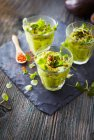 Glasses of avocado cream with chili flakes, cress and parsley — Stock Photo