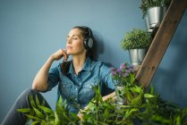 Beautiful woman listening music with headphones at home — Stock Photo