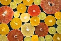 Background of fresh peeled and sliced citrus fruits on dark surface — Stock Photo