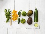 Avocado, pomodori verdi, peperoni Jalapeno, cetriolo, prezzemolo, coltello da cucina e tortilla su legno bianco — Foto stock