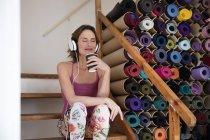 Расслабленная зрелая женщина слушает музыку рядом с ассортиментом ковриков для йоги — стоковое фото