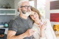 Pareja madura bebiendo café en la cocina en casa - foto de stock