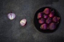 Fresh purple onion in bowl on grey grunge background with halves — Stock Photo