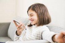 Retrato de niña riendo con auriculares y smartphone en el sofá — Stock Photo