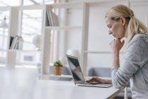 Donna che utilizza il computer portatile alla scrivania in ufficio — Foto stock
