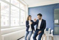 Счастливый бизнесмен и бизнес-леди с напитками в офисе — стоковое фото