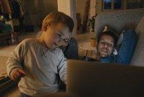 Familia mirando el portátil en el sofá en la oscuridad - foto de stock