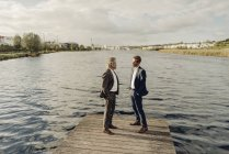 Two businessmen standing on jetty at lake and talking — стоковое фото