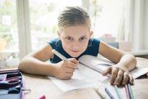 Portrait de fille faisant des devoirs à table — Photo de stock