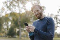 Ritratto di uomo sorridente con cellulare in un parco che guarda la macchina fotografica — Foto stock
