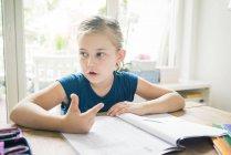 Ragazza facendo i compiti a tavola — Foto stock
